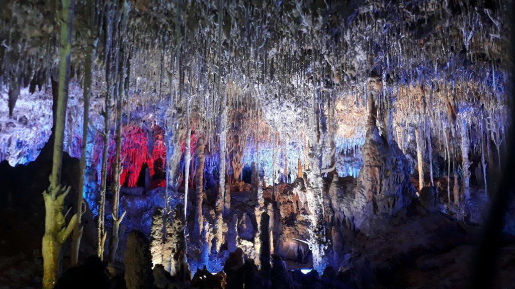Bunt angestrahlte Stalaktiten und Stalagmiten in der Tropfsteinhöhle Coves dels Hams auf Mallorca