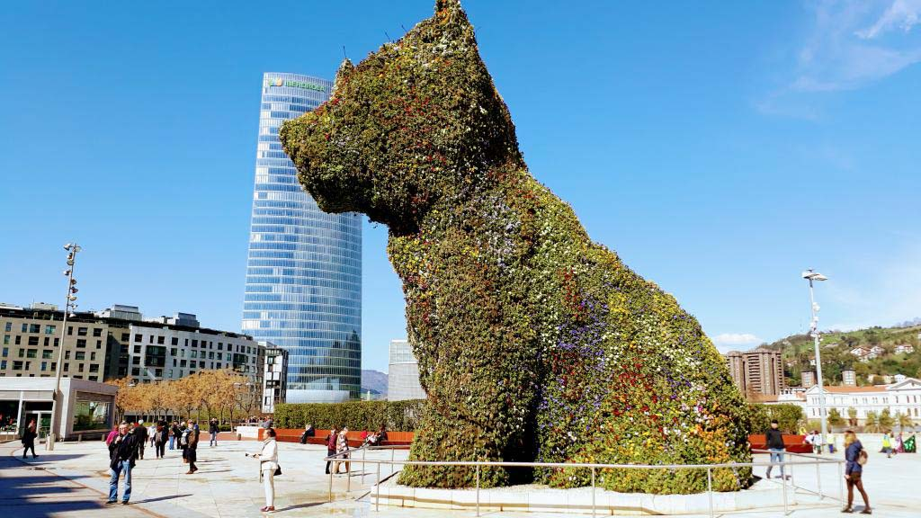 Puppy in front of the Guggenheim Museum with Iberdrola Tower (with 165 meters tallest building in Bilbao) in the background
