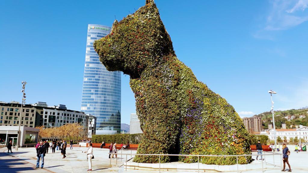 Puppy delante del Museo Guggenheim con la Torre Iberdrola (con 165 metros el edificio más alto de Bilbao) en el fondo