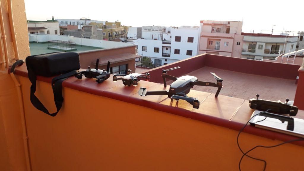 DJI Spark y DJI Mavic Pro, cada uno con control remoto, a la izquierda se puede ver la bolsa del DJI Spark Fly More Combo